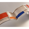 The silver bracelet is decorated with 6 rectangles that are filled with acryl in the well known Mondrian colours red, yellow and blue